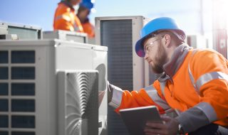 An air conditioning engineer is finishing the installation of several units on a rooftop. Two colleagues can be seen also installing units in the background. They are wearing hi vis jackets, hard hats and safety goggles.